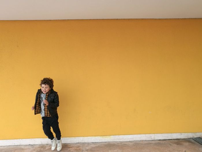 Full length of boy jumping against yellow wall