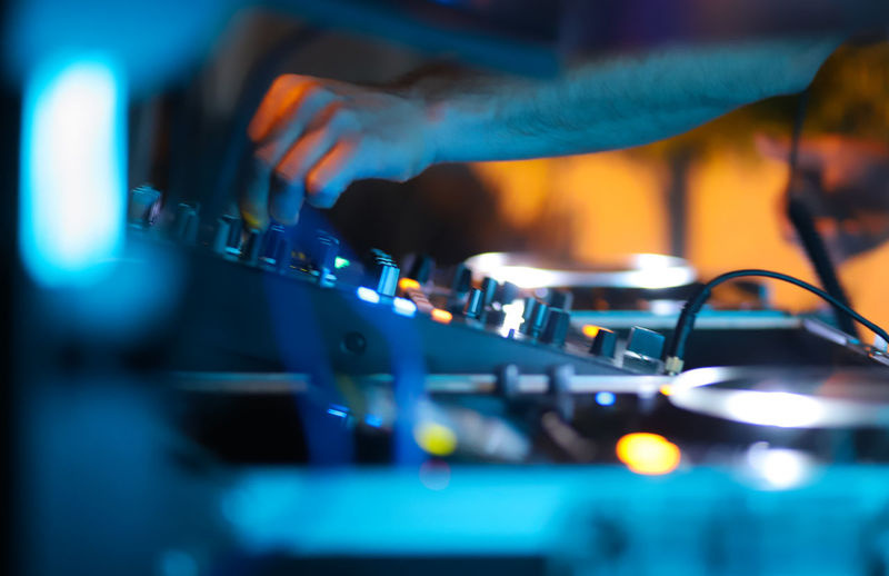 Midsection of man playing music in nightclub