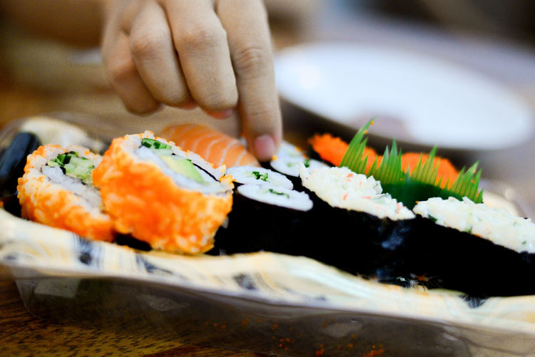 Cropped hand taking sushi served in plate