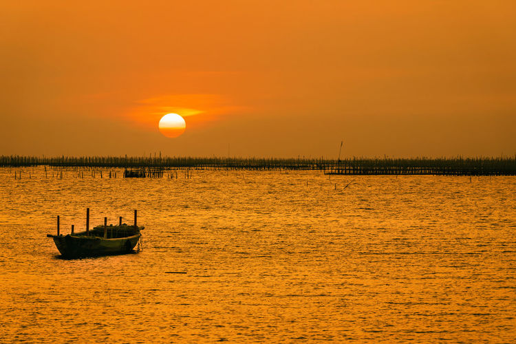 The sunset at  the oyster farm and the little boat. scenic view of sea against sky during sunset