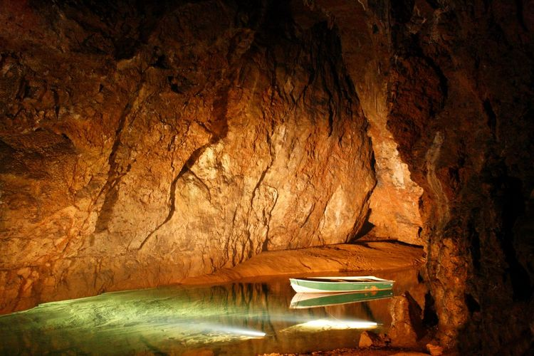 A boat on an underground lake in a cave system in England Cave Cave System Close-up Day Illuminated Indoors  Lake Nature No People Rock - Object Rock Formation Rowboat Underground Lake Underground Water