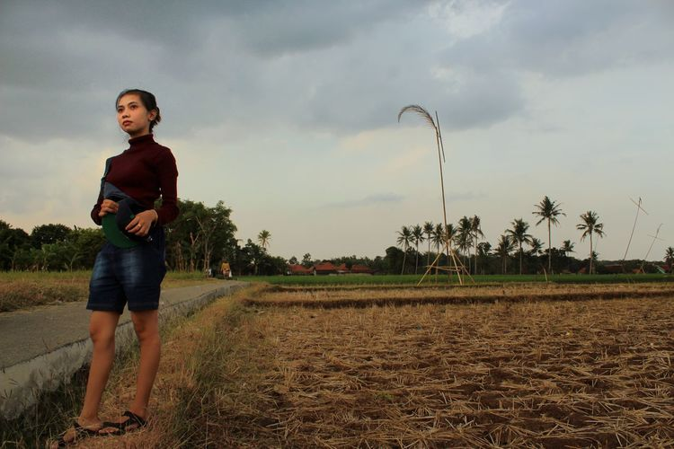 Portrait of happy boy standing on field against sky