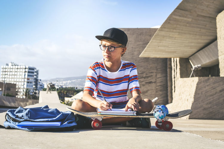 Full length of boy writing in book over skateboard while sitting on road