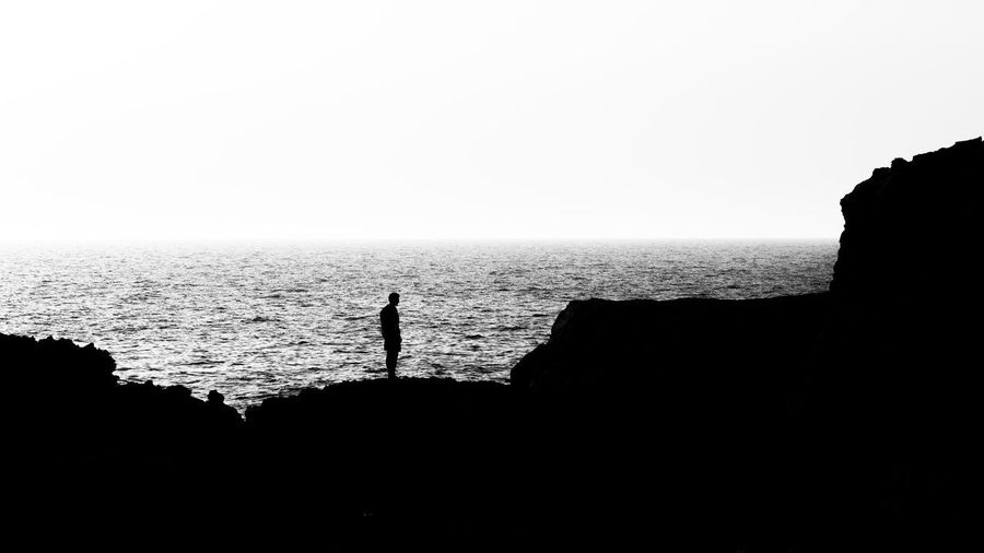 Tarde de siluetas Clear Sky Contemplation Horizon Horizon Over Water One Person Rock Rock - Object Sea Silhouette Standing Tranquility Water