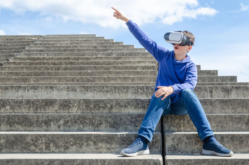 Full length of boy gesturing while wearing virtual reality simulator on staircase against sky