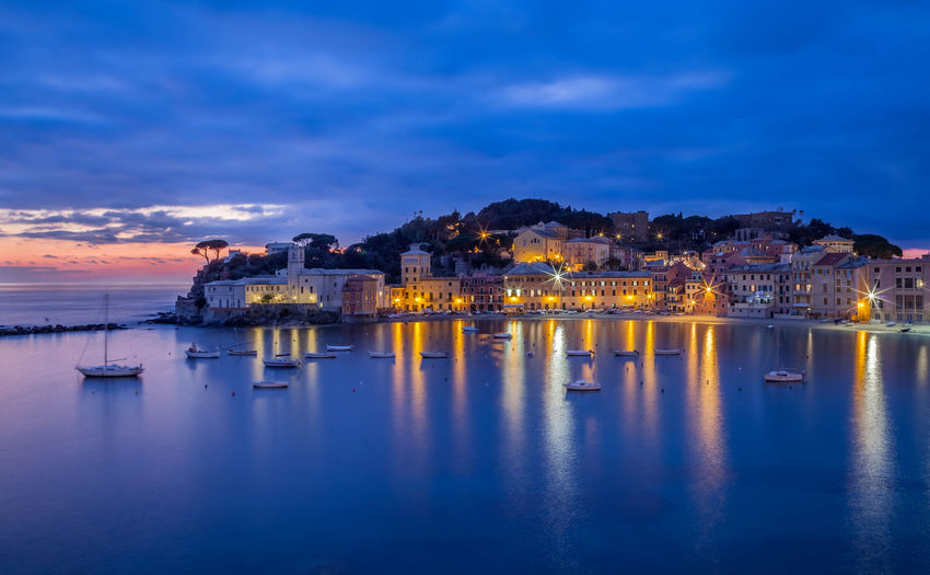 Illuminated city at waterfront during sunset