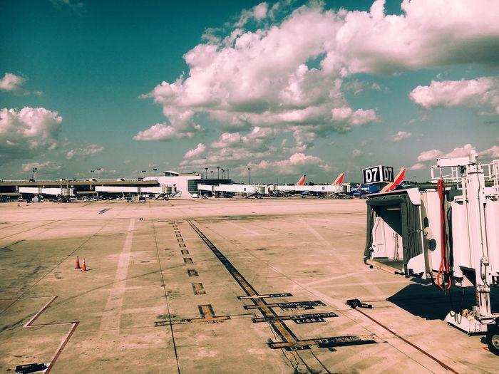 Passenger boarding bridge at airport runway against sky