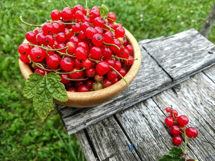 High Angle View Of Red Currants In Bowl On Crate