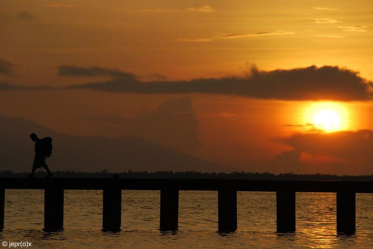 Silhouette of pier in sea at sunset