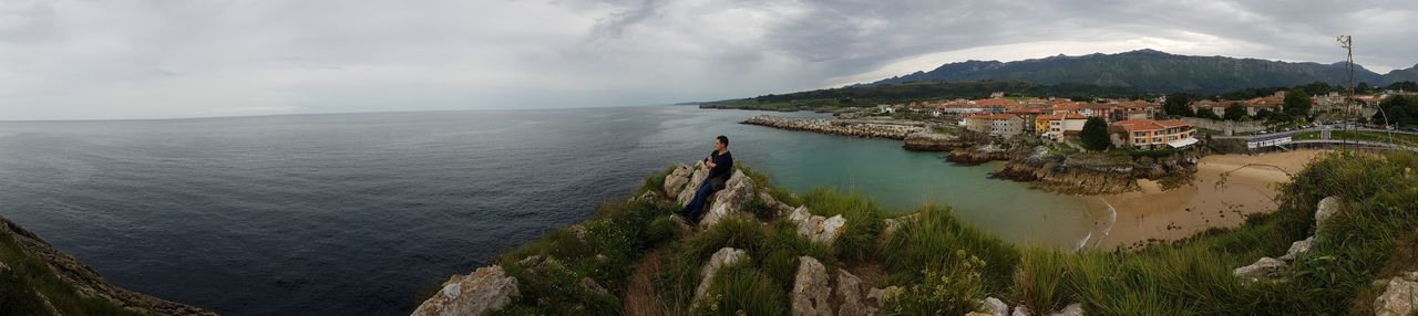 Panoramic view of man sitting on cliff by sea against cloudy sky