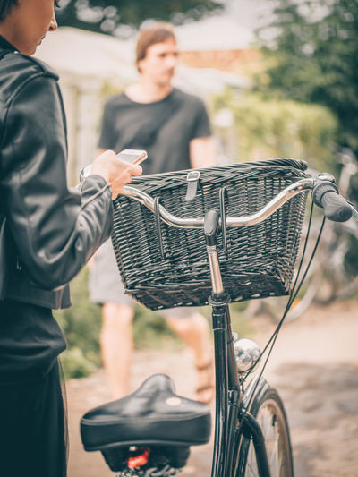 Midsection of man with bicycle on basket