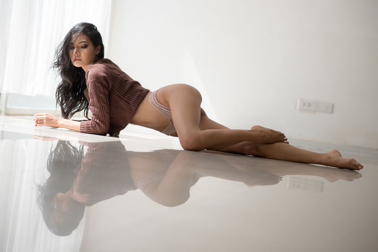 Seductive woman posing on floor at home