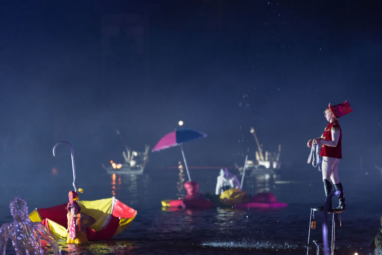 Group of people on boat in water at night