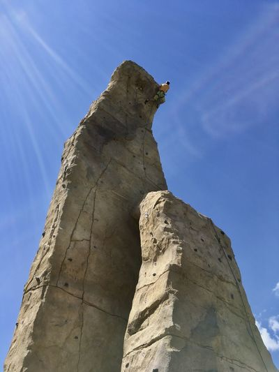 Low angle view of man climbing rock formation against blue sky