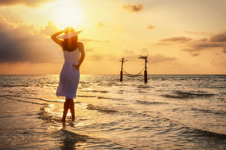 Woman in white summer dress enjoys the sunset over a tropical beach with a hammock Sea Water Sky Sunset One Person Beauty In Nature Standing Cloud - Sky Leisure Activity Beach Arms Raised Rear View Women Horizon Over Water Lifestyles Hammock Travel Traveler Summer Island Tropical Climate Vacations Holiday Enjoying The View Dress