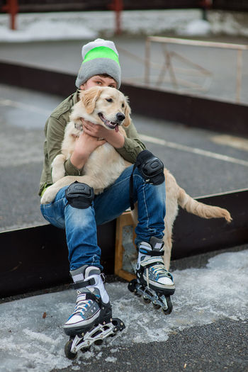Adult Adults Only Baseball Cap Boy Casual Clothing Day Dog Friedship Full Length Golden Retriever Headwear Holding Labrador Retriever Love One Person Outdoors People Puppy Roller Skates Sitting Young Adult