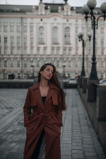 Autumn fashionable female outfit. stylish woman walking in brown coat outdoors. trendy