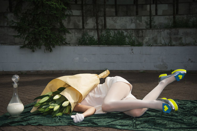 Low section of woman with face covered by flowers lying down