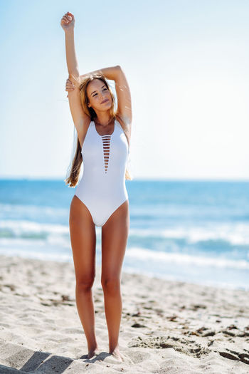 Full length of woman standing in white swimwear at beach against sky