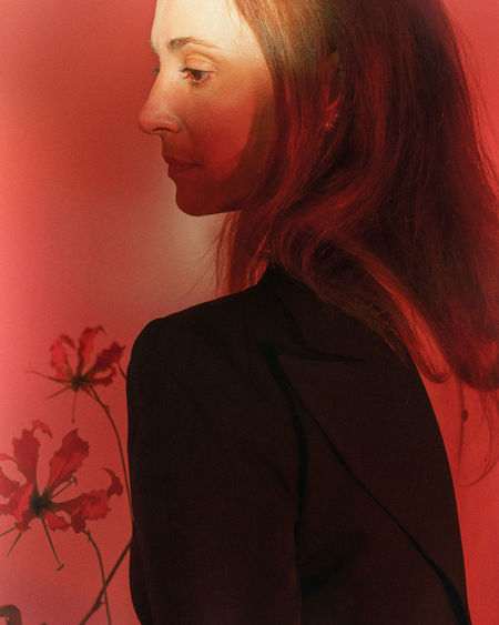 Midsection of woman looking away while standing against red wall