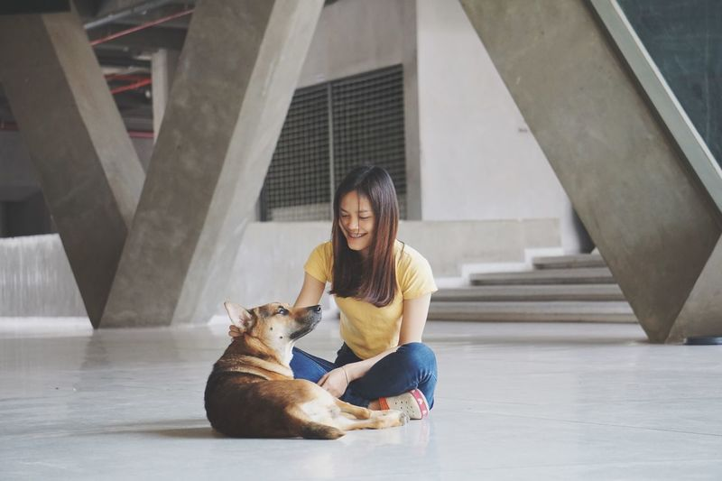 Young Woman With Dog Sitting On Floor