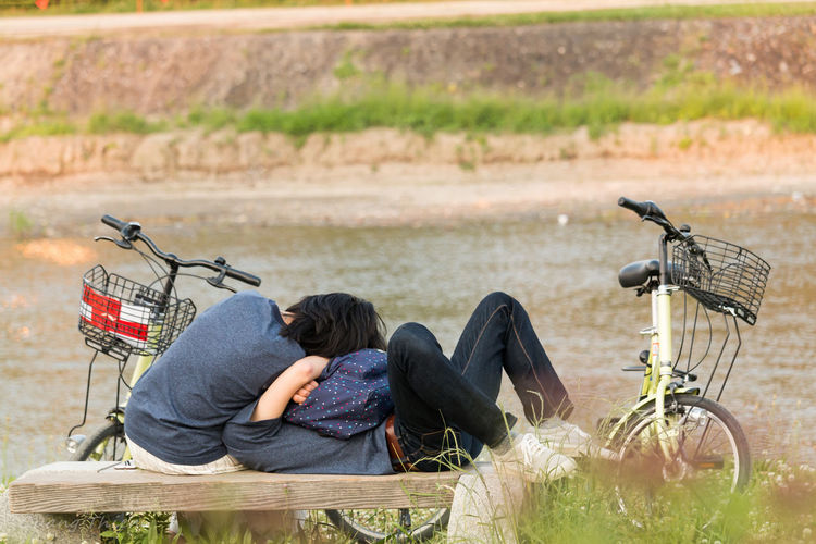Couple relaxing on bench against lake