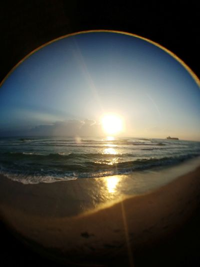 Sunrise through fisheye lens Sea Beach Horizon Over Water Sunlight Sand Water Wave Nature Sun Scenics No People Beauty In Nature Sky Travel Destinations Multicolored Sky Blue Sunbeams Through Clouds Sunrise_Collection Sunrise Wave Fisheyelens