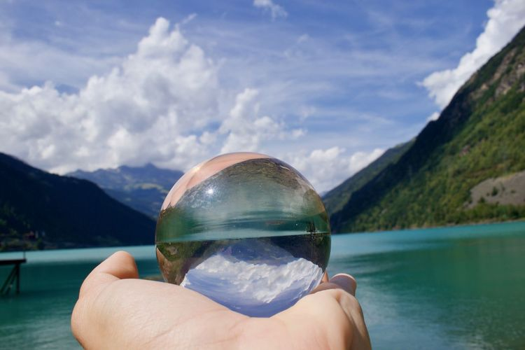 Cropped hand of person holding crystal ball by lake against mountains and sky