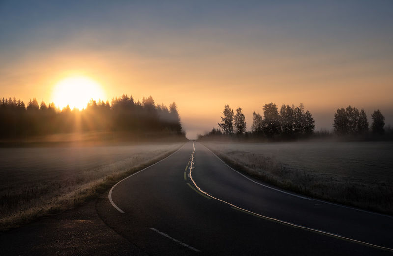 Scenic road landscape with sunrise and fog at autumn morning in Finland Sunset Orange Color The Way Forward Tranquil Scene No People Road Fog Direction Transportation Outdoors Landscape Non-urban Scene Tranquility Beauty In Nature Scenics - Nature Mist Sun Sunrise Asphalt Morning Light Forest Field Meadow Car Atmospheric Mood Capture Tomorrow