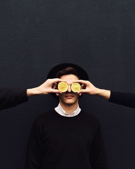 Cropped image of friends covering mans eye with lemon slices