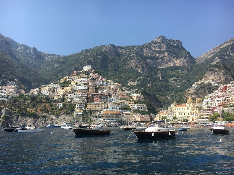 Positano Italy Architecture Water Built Structure Building Exterior Mountain Nautical Vessel Waterfront Transportation Town Residential District Clear Sky Blue City Sea Mode Of Transport In Front Of Day Community Mountain Range Sky