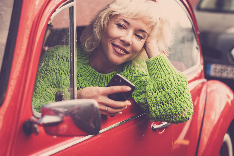 Smiling Woman Using Mobile Phone While Sitting In Car