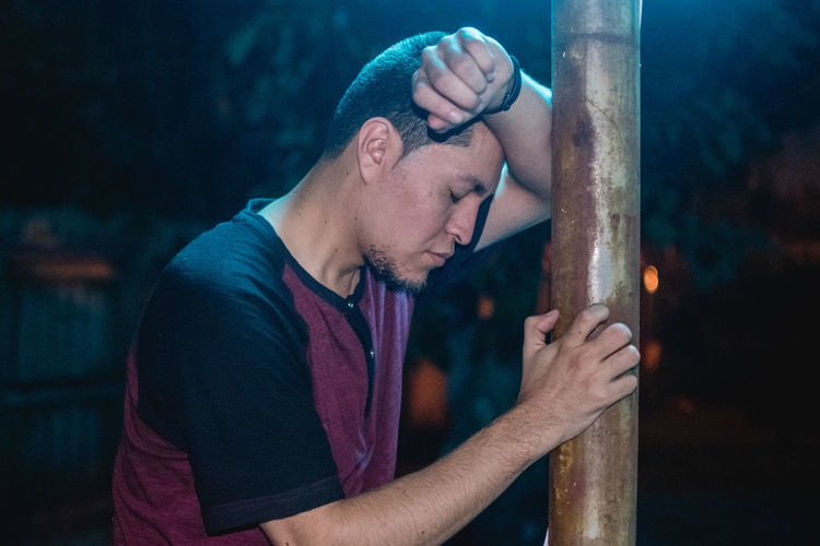 Side View Of Stressed Young Man Leaning On Rod At Night
