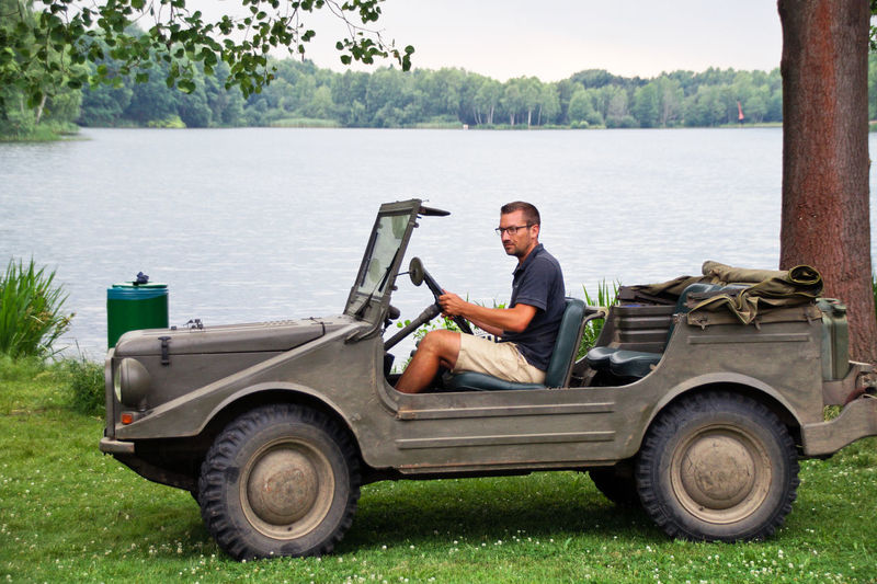 Young man sitting on off-road vehicle on grassy field by lake
