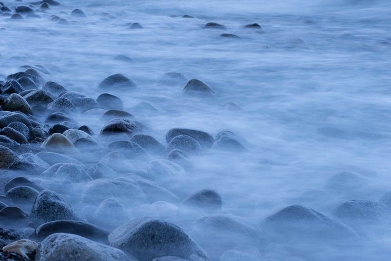 Blurred motion of water over pebbles at night