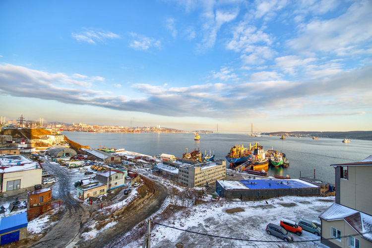 High angle view of buildings by sea against sky during winter
