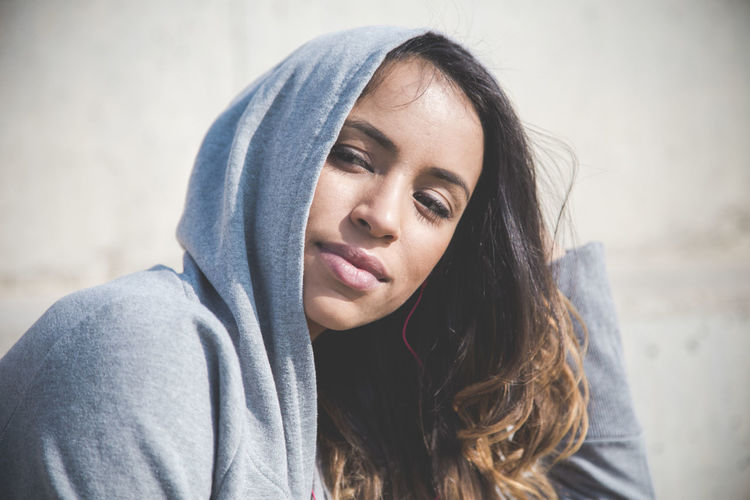 Close-up portrait of beautiful young woman wearing hoodie