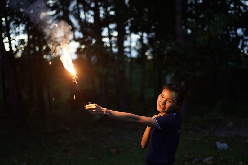 Portrait of woman holding illuminated sparkler on land against trees