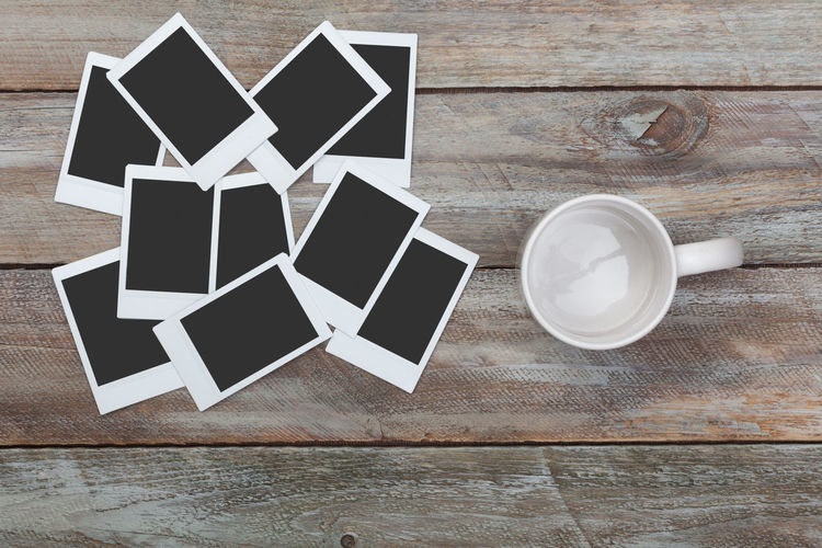 Empty coffee mug and heap of blank instant photos on wood table with copy space Bird's Eye View Close-up Coffee Concept Copy Space Cup Desktop Empty Frame High Angle View Images Instant Mug No People Nobody Photo Photography Photos Polaroid Still Life Table Vintage Wood