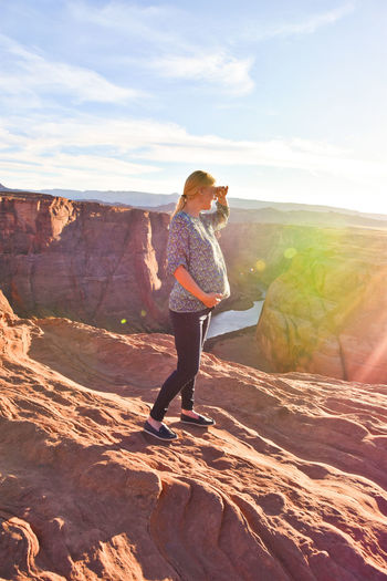Full length of pregnant woman standing on rock at horseshoe bend against sky