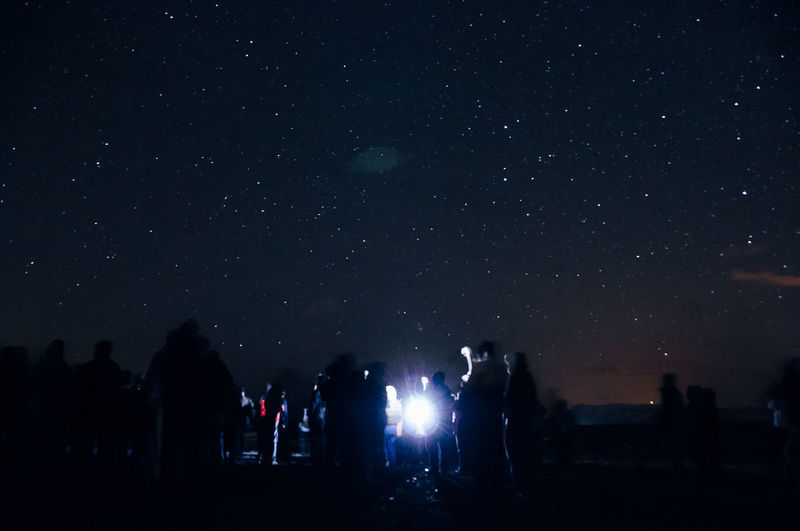 Silhouette people against illuminated star field against sky at night
