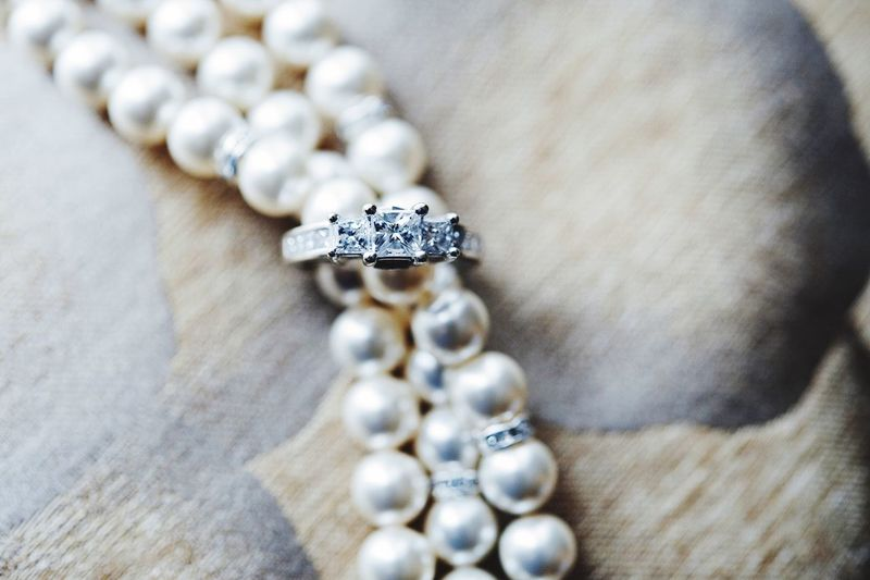 Close-Up Of Engagement Ring And Pearl Necklace