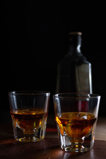Close-up of whiskey glasses on table against black background