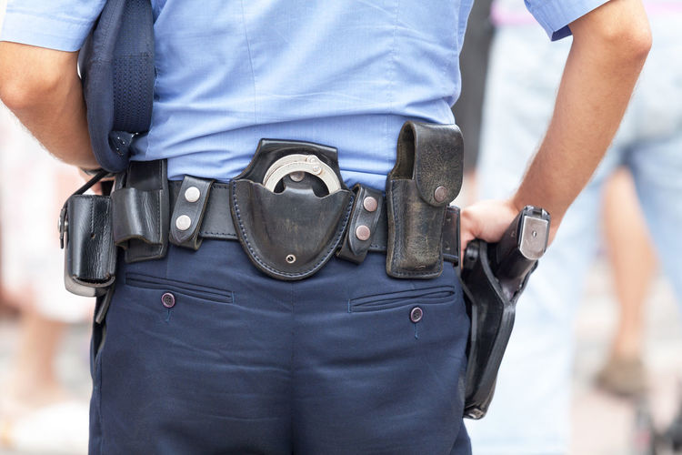 Midsection rear view of police man with belt with handcuffs and gun