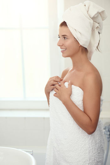 Happy young woman in her bathroom Beautiful Woman Beauty Indoors  One Person Young Adult Towel Wrapped In A Towel Adult Real People Woman Happy Enjoying Life Bathroom Domestic Life Home Shower Clean Freshness Domestic Bathroom Hygiene Lifestyles Body Care Domestic Room Smiling Routine