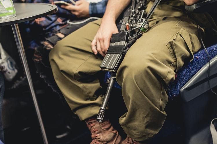 Peace Sitting Soldier Army Gun Holding Human Hand Human Leg Israel Low Section Men Midsection Military Occupation People Real People Safety Train War Weapon