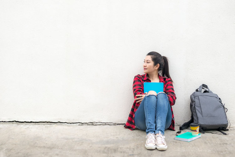 Young woman looking away while sitting on wall