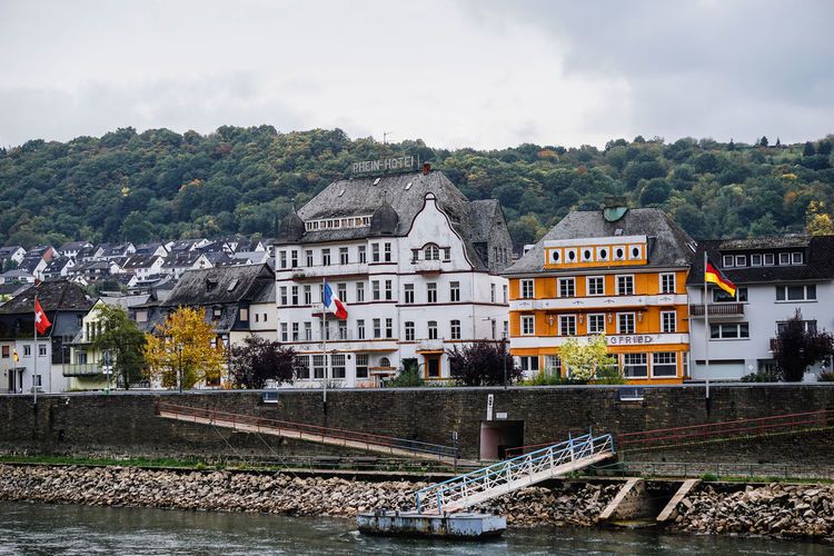 Houses in town by rhine river against sky