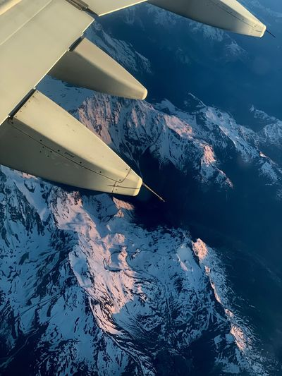 High angle view of airplane flying over snowcapped mountains