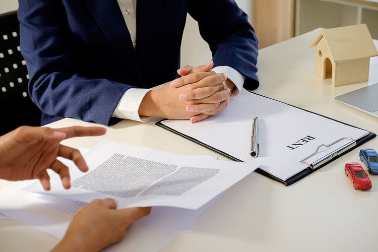 Cropped Hands Of Real Estate Agent Showing Form To Client Sitting At Desk